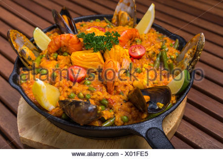 mediterranean paella with seafood in frying pan on wooden board - Stock Photo