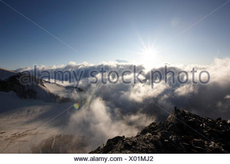 View over cloud-covered valley in sunrise, Saas-Fee, Canton of Valais, Switzerland - Stock Photo