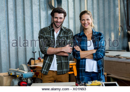 Portrait of carpenters standing with arms crossed - Stock Photo