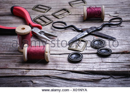Buttons and fasteners from outdated clothes on wooden background - Stock Photo