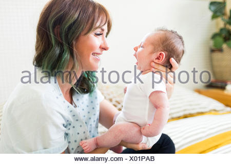 Smiling mother holding baby boy (6-11 months) - Stock Photo