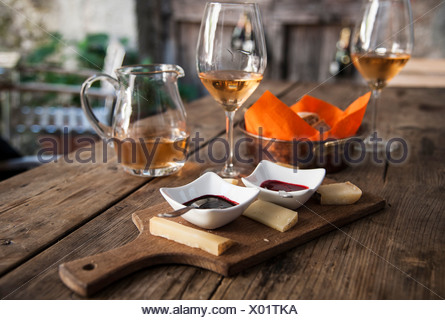 Cheese platter with dips, bread basket, wine glasses and wine jug, Tirano, Sondrio province, Lombardy, Italy - Stock Photo