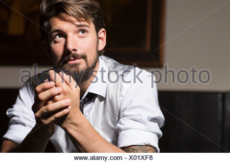 Portrait of man with hands clasped - Stock Photo