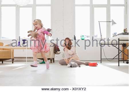 A young girl carrying a stuffed toy in her mouth running around - Stock Photo
