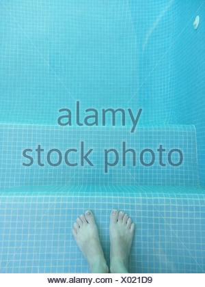 Boy's feet in swimming pool - Stock Photo