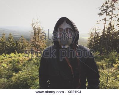 Front View Of Man Wearing Gas Mask In Forest Against Clear Sky - Stock Photo