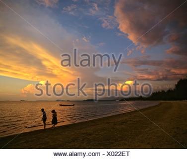 Evening light, two children on a beach, Kota Kinabalu, Borneo, Malaysia - Stock Photo