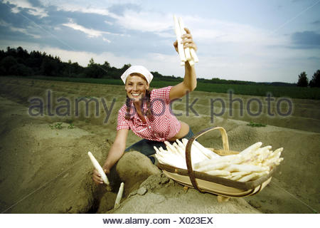 Asparagus field, woman, young, asparagus, harvest field, asparagus cultivation, agriculture, country living, vegetables, vegetable-growing, cultivation, land life, farmer, harvest, yield, asparagus harvest, asparagus sticks, basket, sting, vegetable asparagi, work, ground, earthworks, happy, smile, kneel, hold up, headscarf, headgear - Stock Photo