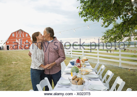 Senior couple kissing by dinner table at outdoor farm party - Stock Photo