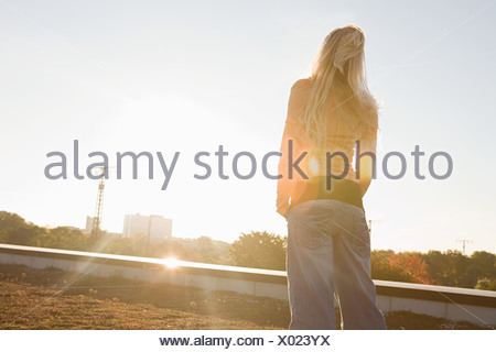 Young woman looking toward the sun - Stock Photo