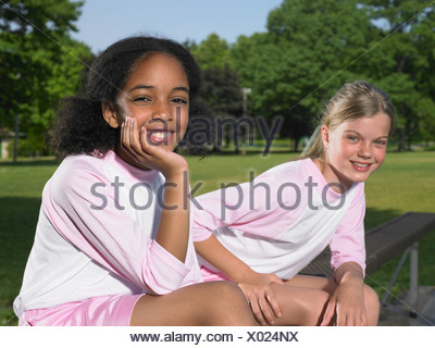 Two girls sat on a bench - Stock Photo