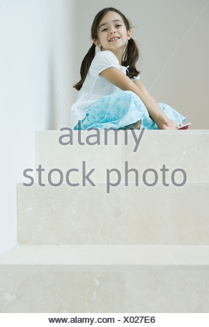 Girl sitting on steps playing with top, smiling at camera, low angle view - Stock Photo