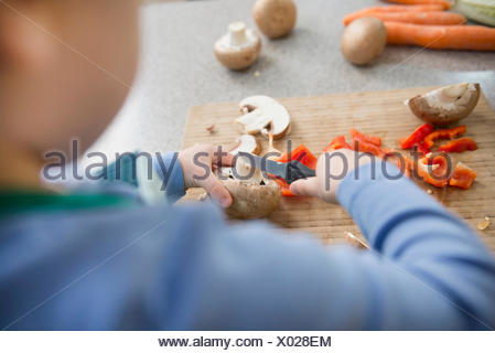 Boy cutting mushrooms on chopping board, close up - Stock Photo