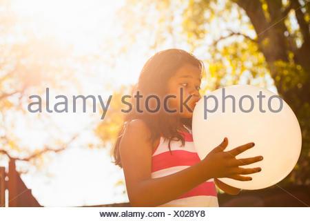 Girl blowing up balloon in garden - Stock Photo
