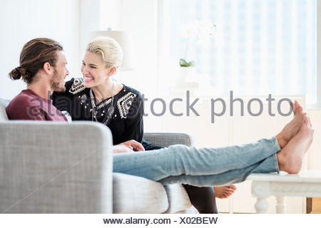 Couple laughing on sofa - Stock Photo