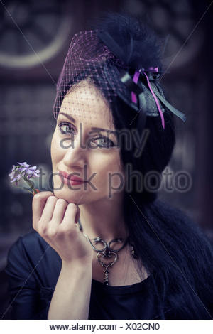 Portrait of a woman holding a flower - Stock Photo