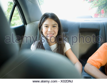 Brother and sister sitting in back seat of car - Stock Photo