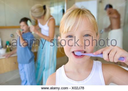 Girl  brushing her teeth in bathroom, portrait, family in background - Stock Photo