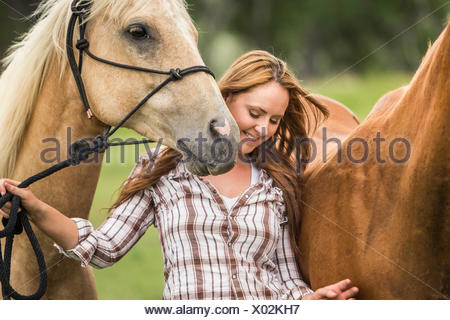 Young woman walking with two horses, smiling - Stock Photo