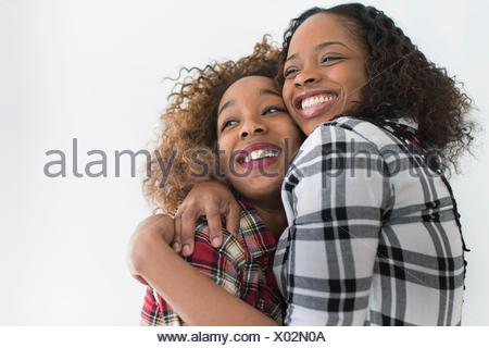 Studio portrait of two young women friends hugging - Stock Photo