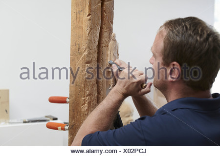 Worker chiseling figure from wood