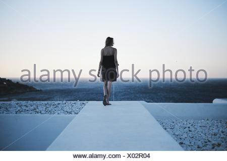 Rear view of woman looking out to sea - Stock Photo