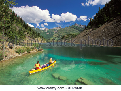 Young couple canoeing on Lower Silver Springs Lake in Elk Valley near Fernie, East Kootenays, British Columbia, Canada. - Stock Photo