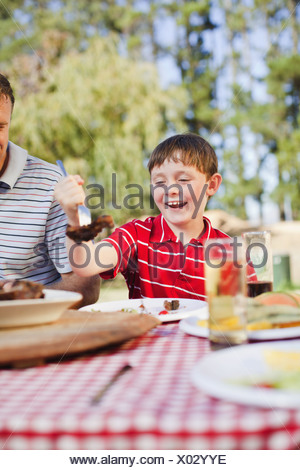 Boy serving himself meat at picnic table - Stock Photo