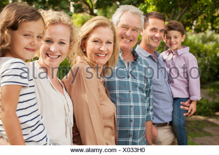 Portrait of multi-generation family smiling outdoors - Stock Photo