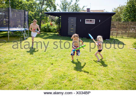 Siblings (8-9, 10-11) playing with water guns in backyard - Stock Photo