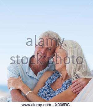 Senior couple hugging on patio - Stock Photo