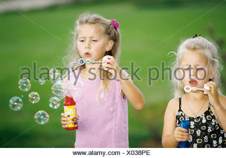 little girls making soap bubbles - Stock Photo