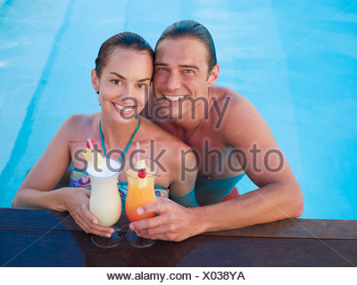 Couple in swimming pool with tropical cocktails - Stock Photo