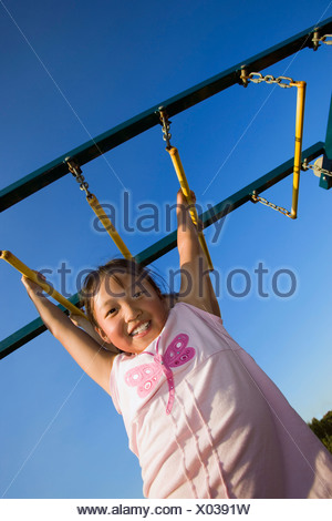 A young girl hanging from bar - Stock Photo