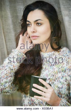 Woman drinking cup of coffee by window - Stock Photo