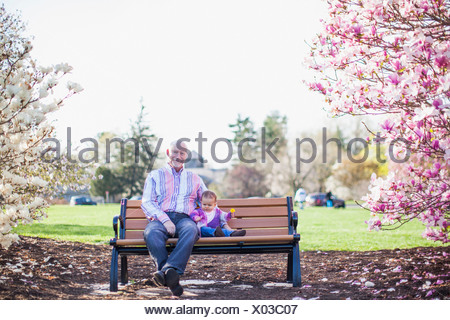 Grandfather and granddaughter sitting on park bench - Stock Photo