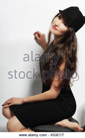 Authentic Woman in Black Dress and Woolen Cap - Stock Photo