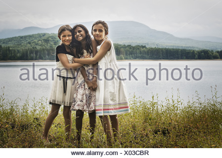 Three young girls standing by the side of a lake hugging each other Woodstock New York USA - Stock Photo