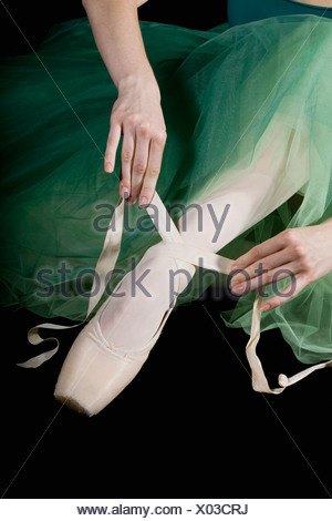 The hands of ballet dancer tying a pointe shoe - Stock Photo