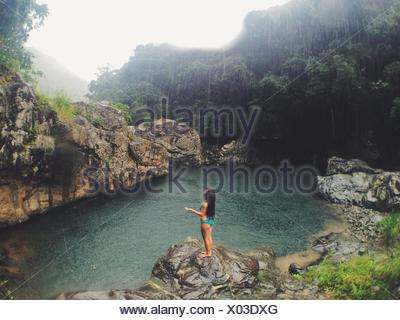 Woman standing on rock in rain - Stock Photo