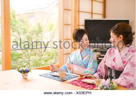 Two young women wearing yukata talking - Stock Photo