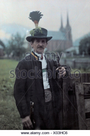 A man in Pongau field and forest guard uniform poses with his pipe. - Stock Photo