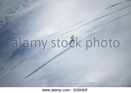 rapid downhill skiing with snowboard in the deep snow - Stock Photo