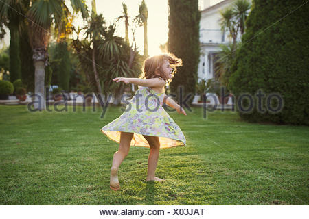 Girl spinning around in garden - Stock Photo