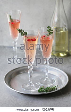 Pomegranate champagne in glasses with fresh thyme decoration - Stock Photo