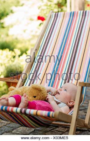 Baby girl sitting on deck chair with teddy bear - Stock Photo