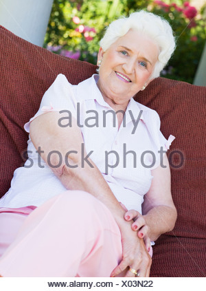 Senior woman sitting outdoors on a chair - Stock Photo