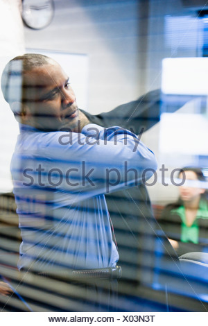 Businessman putting on his jacket viewed through conference room window - Stock Photo