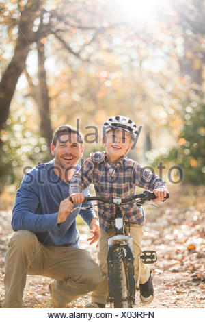 Portrait smiling father teaching son to ride a bike in woods - Stock Photo