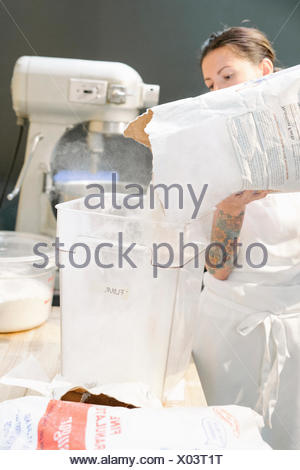 Woman wearing a white apron at a work counter in a bakery, pouring flour into a container. - Stock Photo